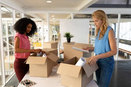 Foto de Side view of young diverse female executives unpacking cardboard boxes in office. This is a casual creative start-up business office for a diverse team - Imagen libre de derechos
