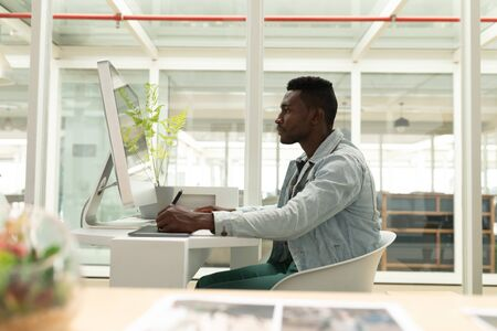 Foto de Side view of African american male graphic designer using graphic tablet at desk in office. This is a casual creative start-up business office for a diverse team - Imagen libre de derechos