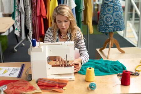 Front view of Caucasian female fashion designer using sewing machine on a table in design studio. This is a casual creative start-up business office for a diverse team