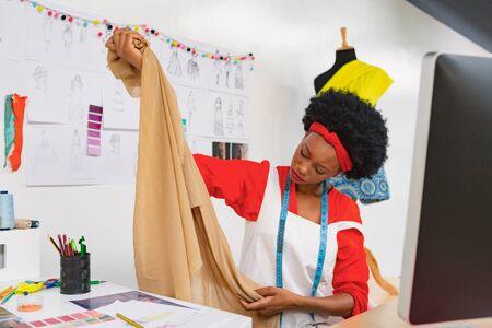 Foto de Front view of beautiful mixed race female fashion designer checking a textile cloth at desk in design studio. Modern casual creative fashion design business concept - Imagen libre de derechos