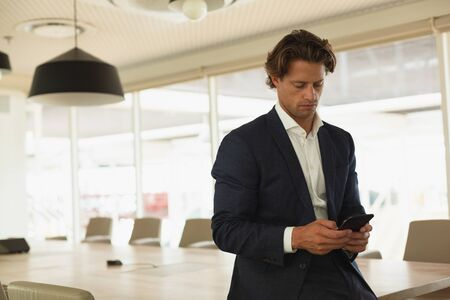 Photo pour Front view of handsome Caucasian businessman using mobile phone in the conference room at office. New start-up business with entrepreneur working hard - image libre de droit