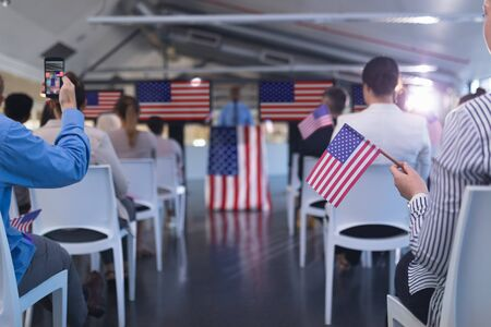 Foto de Front view of diverse business people waving an American flag in business seminar. International diverse corporate business partnership concept - Imagen libre de derechos