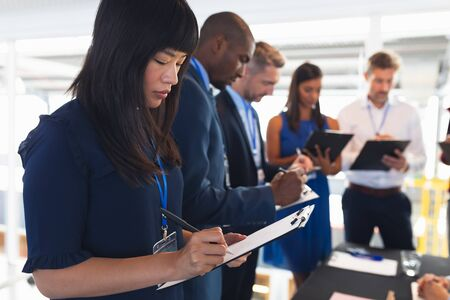 Photo pour Side view of diverse Business people checking in at conference registration table. International diverse corporate business partnership concept - image libre de droit