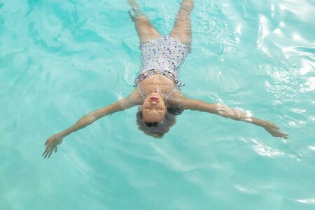 Overhead of Caucasian woman with eyes closed floating in swimming pool at the backyard of home. Summer fun at home by the swimming pool