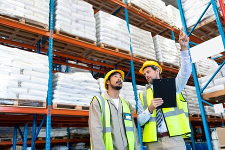 Front view of handsome Caucasian male supervisor standing with Asian worker and pointing at distance in warehouse. This is a freight transportation and distribution warehouse. Industrial and industrial workers concept
