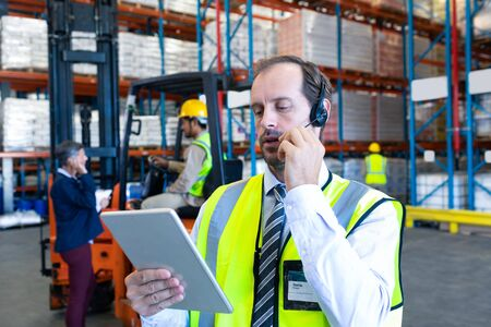 Photo pour Close-up of handsome Caucasian male supervisor using digital tablet while talking on headset in warehouse. Diverse colleagues communicating in the background. This is a freight transportation and distribution warehouse. Industrial and industrial workers concept - image libre de droit
