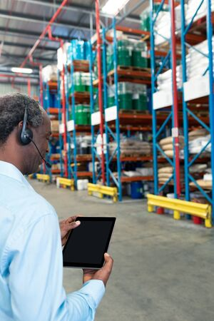 Rear view of mature African-american male supervisor with headset using digital tablet in warehouse. This is a freight transportation and distribution warehouse. Industrial and industrial workers concept