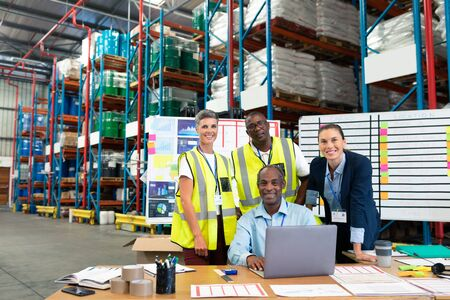 Front view of mature African-american male supervisor with his diverse coworkers discussing over laptop at desk in warehouse. This is a freight transportation and distribution warehouse. Industrial and industrial workers concept