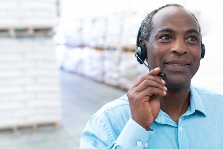 Foto de Portrait close-up of handsome mature African-american male supervisor talking on headset in warehouse. This is a freight transportation and distribution warehouse. Industrial and industrial workers concept - Imagen libre de derechos