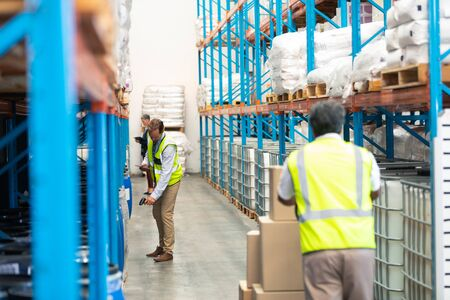 Photo pour Rear view of mature Asian male worker pulling pallet jack with cardboard boxes while diverse supervisors work in the aisle in warehouse. This is a freight transportation and distribution warehouse. Industrial and industrial workers concept - image libre de droit