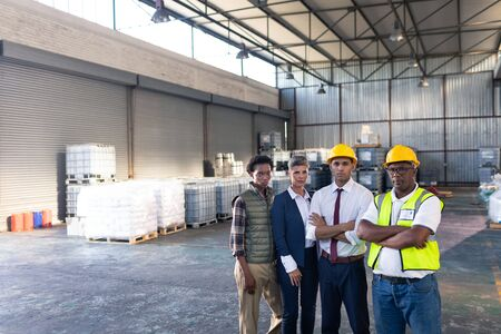 Portrait of diverse male and female staffs standing together in warehouse. This is a freight transportation and distribution warehouse. Industrial and industrial workers concept