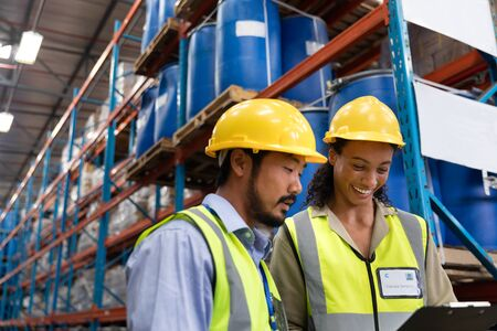 Photo pour Low angle view of male and female worker discussing on clipboard in warehouse. This is a freight transportation and distribution warehouse. Industrial and industrial workers concept - image libre de droit