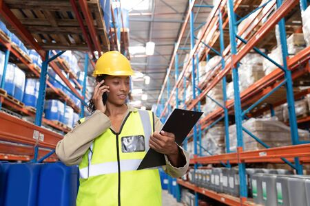 Photo for Front view of female worker looking at clipboard while talking on mobile phone in warehouse. This is a freight transportation and distribution warehouse. Industrial and industrial workers concept - Royalty Free Image