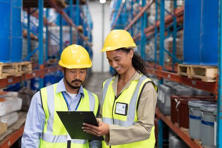 Photo pour Front view of male and female worker discussing on clipboard in warehouse. This is a freight transportation and distribution warehouse. Industrial and industrial workers concept - image libre de droit