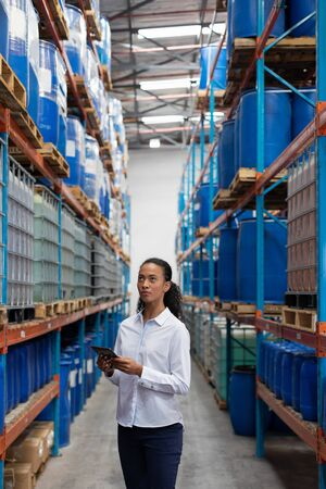 African American female manager using digital tablet while checking stocks in warehouse. This is a freight transportation and distribution warehouse. Industrial and industrial workers concept
