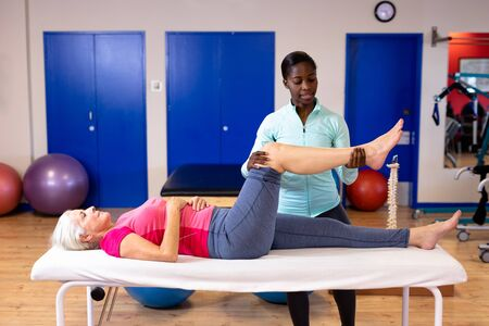 Photo pour Female physiotherapist giving leg massage to active senior woman in sports center. Sports Rehab Centre with physiotherapists and patients working together towards healing - image libre de droit