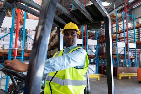Photo for Front view of male worker looking at camera while driving forklift in warehouse. This is a freight transportation and distribution warehouse. Industrial and industrial workers concept - Royalty Free Image