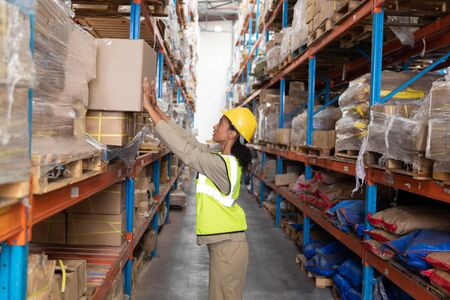 Photo for Side view of female worker putting cardboard box on a rack in warehouse. This is a freight transportation and distribution warehouse. Industrial and industrial workers concept - Royalty Free Image