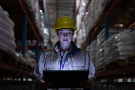 Front view of female worker working on digital tablet on warehouse. This is a freight transportation and distribution warehouse. Industrial and industrial workers concept