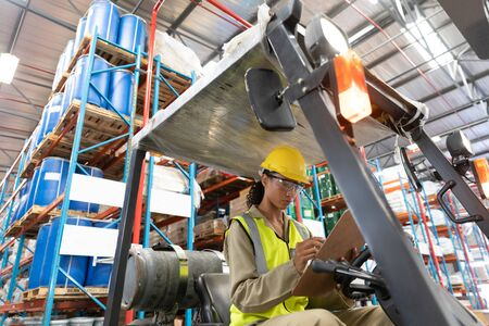 Photo for Low angle view of female staff writing on clipboard while sitting on forklift in warehouse. This is a freight transportation and distribution warehouse. Industrial and industrial workers concept - Royalty Free Image