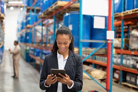 Happy female manager using digital tablet in warehouse. This is a freight transportation and distribution warehouse. Industrial and industrial workers concept