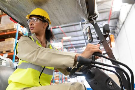 Photo pour Low angle view of female staff driving forklift in warehouse. This is a freight transportation and distribution warehouse. Industrial and industrial workers concept - image libre de droit