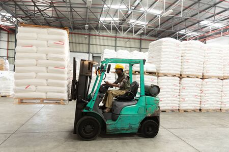 Photo for Side view of female worker driving forklift in warehouse. This is a freight transportation and distribution warehouse. Industrial and industrial workers concept - Royalty Free Image
