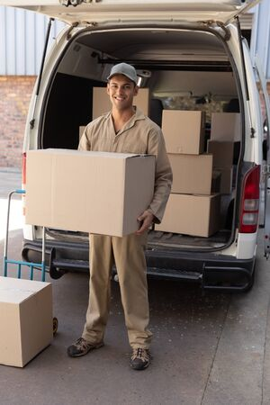 Photo for Front view of delivery man carrying cardboard boxes outside the warehouse. This is a freight transportation and distribution warehouse. Industrial and industrial workers concept - Royalty Free Image