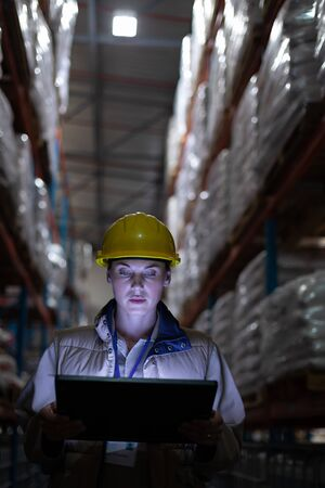 Close-up of female staff using digital tablet in warehouse. This is a freight transportation and distribution warehouse. Industrial and industrial workers concept