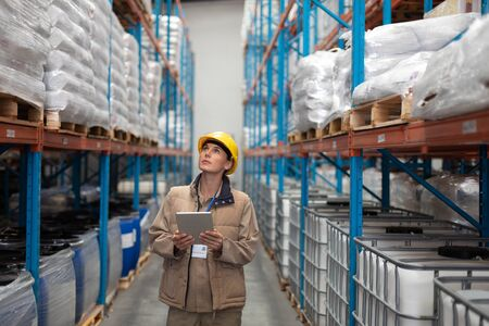 Front view of female worker with digital tablet looking up in warehouse. This is a freight transportation and distribution warehouse. Industrial and industrial workers concept