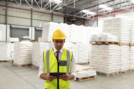 Front view of male manager working on digital tablet in warehouse. This is a freight transportation and distribution warehouse. Industrial and industrial workers concept