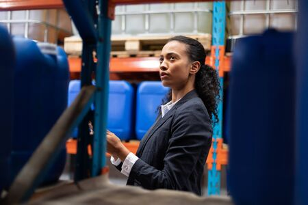 Foto de Side view of female manager checking stocks in warehouse. This is a freight transportation and distribution warehouse. Industrial and industrial workers concept - Imagen libre de derechos