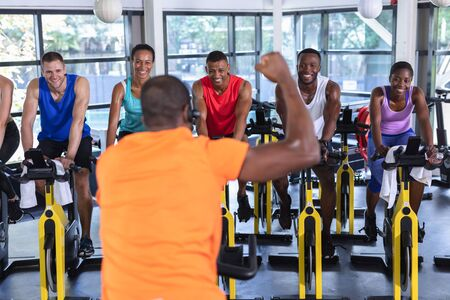 Rear view of African-american Male trainer training people to work out on exercise bike in fitness center. Bright modern gym with fit healthy people working out and training at spin class
