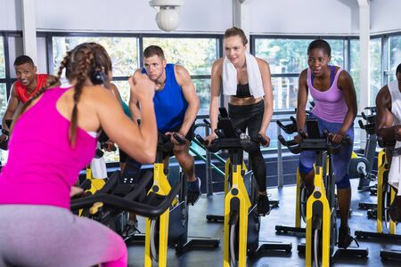 Rear view of Caucasian Female trainer training people to work out on exercise bike in fitness center. Bright modern gym with fit healthy people working out and training at spin class