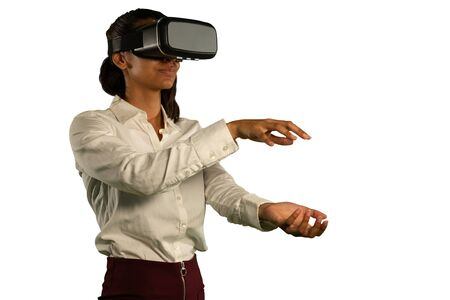 Foto de Side view close up of a young mixed race woman wearing a white shirt and a VR headset, looking ahead with hands held out in front of her one above the other, as if holding or touching - Imagen libre de derechos
