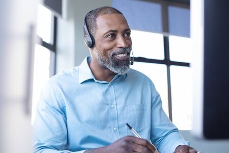 Photo pour Front view close up of an African American male business creative working in a casual modern office, making notes, smiling and talking on a phone headset - image libre de droit