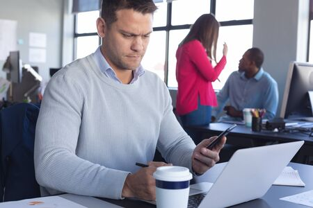 Foto de Front view close up of a Caucasian male business creative working in a casual modern office, using a laptop and looking at his smartphone, with colleagues in the background - Imagen libre de derechos