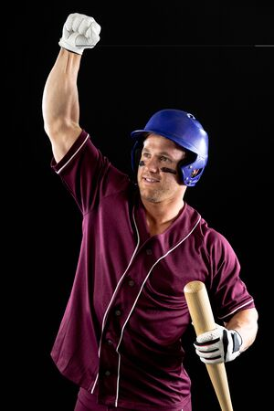 Photo pour Front view close up of a Caucasian male baseball player, a hitter wearing a team uniform, a helmet and holding a baseball bat, with fist raised in celebration of a victory. Vertical shot - image libre de droit