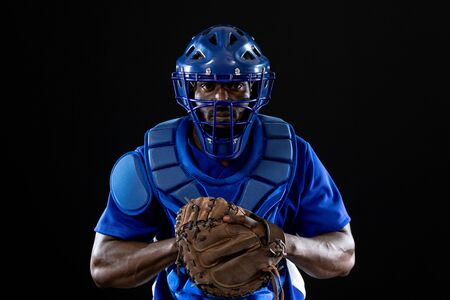 Foto de Front view of an African American male baseball player, a catcher, wearing a team uniform, protective clothing, a helmet and a mitt, ready for a pitch - Imagen libre de derechos