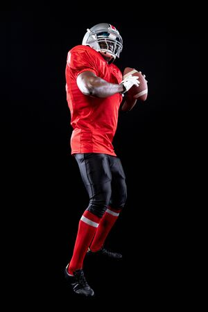 Photo for Side view close up of an African American male American football player wearing a team uniform, pads and a helmet, holding a football in both hands - Royalty Free Image