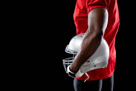 Photo pour Side view mid section of an African American male American football player wearing a team uniform, pads and gloves, holding a helmet under his arm - image libre de droit
