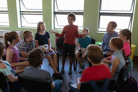 Foto de Front view of a diverse group of elementary school kids sitting on chairs in a circle and interacting during a lesson, one African American girl standing and talking while her classmates and male Caucasian teacher sit and listen - Imagen libre de derechos