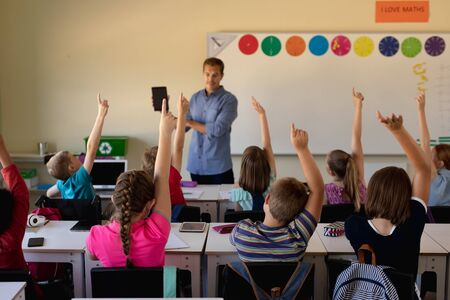Photo pour Front view of a Caucasian male school teacher standing in front of the class holding a tablet computer and addressing a diverse group of schoolchildren, sitting at desks and raising their hands to answer a question during a lesson in an elementary school classroom - image libre de droit