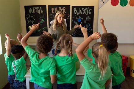 Photo pour Front view of a Caucasian female school teacher with long blonde hair pointing to a recycling poster and a diverse group of schoolchildren wearing green t shirts seen from behind, raising their hands to answer a question during a lesson in an elementary school classroom - image libre de droit