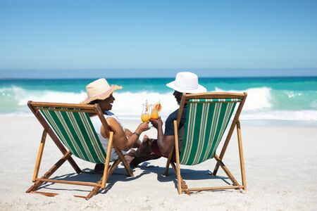 Photo for Rear view of a senior African American couple on a beach in the sun, sitting in deckchairs, wearing sun hats, holding cocktails and making a toast, with blue sky and calm sea in the background - Royalty Free Image