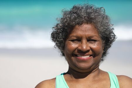 Portrait of a senior Africna American woman with short grey curly hair on a beach in the sun, smiling to camera