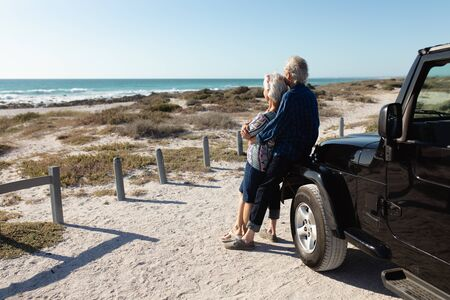 Photo pour Side view of a senior Caucasian couple at the beach in the sun, standing and embracing, leaning against their car and admiring the view - image libre de droit