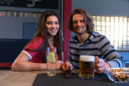 Photo for Portrait of a Caucasian woman and man sitting together at the bar in a pub during the day, looking to camera and smiling, with drinks and snacks on the bar in front of them - Royalty Free Image