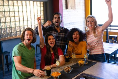 Photo pour Front view of a group of five multi-ethnic male and female friends at the bar in a pub with arms in the air, cheering, having fun and celebrating while watching a sports game on TV, smiling and laughing together - image libre de droit