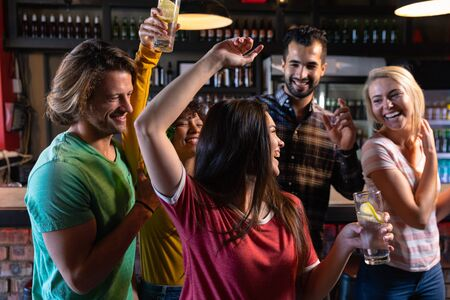 Photo pour Front view of a group of five multi-ethnic male and female friends at the bar in a pub holding drinks, dancing and having fun and celebrating, two women with arms in the air and all of them smiling and laughing together - image libre de droit